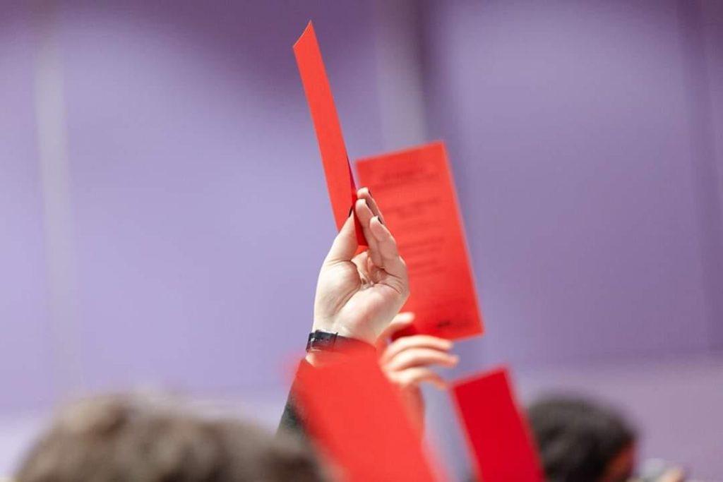 Eine Hand mit einer roten Abstimmungskarte
